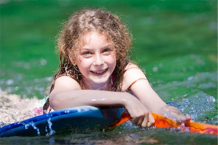 A young girl floating on a body board Stock Photo - Premium Royalty-Free, Code: 618-03612895