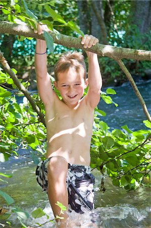 A young boy swinging from a branch over a river Stock Photo - Premium Royalty-Free, Code: 618-03612891