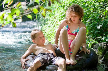preteen girl wet clothes - Two children floating down a river together on an inflatable ring Stock Photo - Premium Royalty-Free, Code: 618-03612893