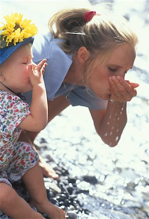 Mother and daughter scoop water from stream, drink Stock Photo - Premium Royalty-Free, Code: 618-03630725