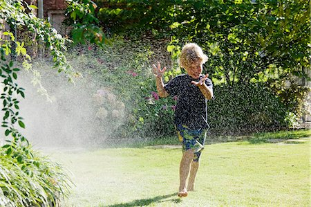 young boy running through sprinkler Stock Photo - Premium Royalty-Free, Code: 618-03630818
