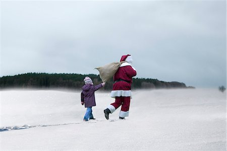 Child walking behind Santa Claus through snowy field Stock Photo - Premium Royalty-Free, Code: 618-03631910