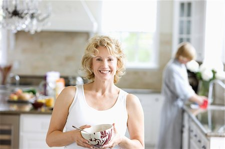 Portrait of Woman with bowl of cereal, in kitchen. Stock Photo - Premium Royalty-Free, Code: 618-03632839