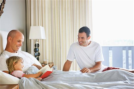 Two Men reading to Young Girl in bed. Stock Photo - Premium Royalty-Free, Code: 618-03632876