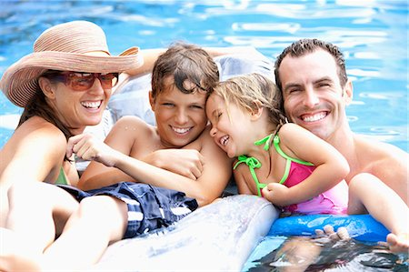 preteen girl wet clothes - Portrait of young family in swimming pool. Stock Photo - Premium Royalty-Free, Code: 618-03632883