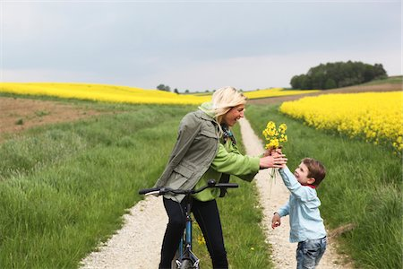 Young boy giving mother on bicycle yellow flowers Stock Photo - Premium Royalty-Free, Code: 618-03780449