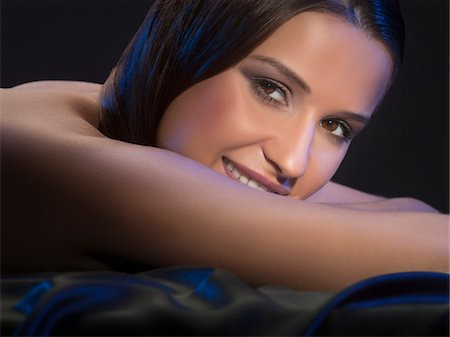 Close-up portrait of young sexy woman lying in satin sheets, studio shot Stock Photo - Premium Royalty-Free, Code: 618-03780478