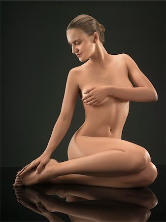 Portrait of young nude woman sitting and posing, studio shot Stock Photo - Premium Royalty-Free, Code: 618-03780489