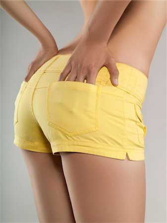Close-up view of young woman wearing short yellow shorts with hands in pockets, studio shot Stock Photo - Premium Royalty-Free, Code: 618-03780482