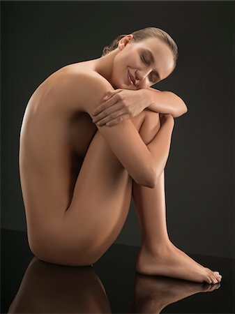 Portrait of young nude woman sitting and hugging herself, studio shot Stock Photo - Premium Royalty-Free, Code: 618-03780490
