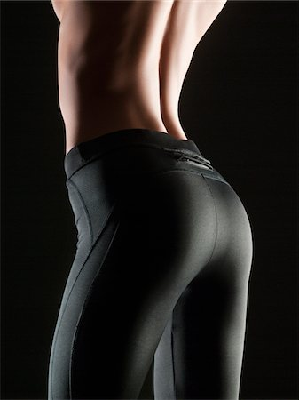 Close-up of topless young woman wearing black stretch pants, studio shot Stock Photo - Premium Royalty-Free, Code: 618-03780555