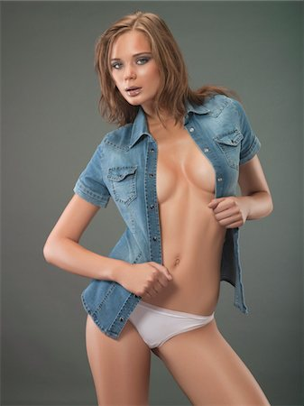 female nude breast sexy - Portrait of young sexy woman with unbuttoned denim shirt, studio shot Stock Photo - Premium Royalty-Free, Code: 618-03780578