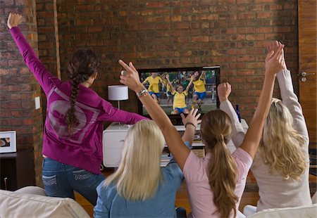 soccer fan - Young women cheering and watching women's soccer game on TV Stock Photo - Premium Royalty-Free, Code: 618-03848458