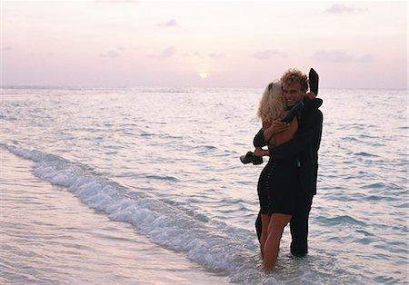 Young couple huging at the water's edge, Kuredo, Maldives. Stock Photo - Premium Royalty-Free, Code: 6102-03751116
