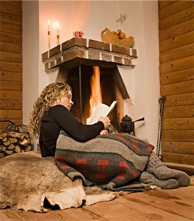 sweater and fireplace - A woman reading a book in front of a fireplace, Sweden. Stock Photo - Premium Royalty-Free, Code: 6102-03826955