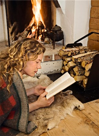 sweater and fireplace - A woman reading infront of  a fireplace, Sweden. Stock Photo - Premium Royalty-Free, Code: 6102-03826956