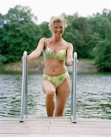 A woman getting out of the water, Sweden. Stock Photo - Premium Royalty-Free, Code: 6102-03827846