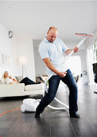 A man pretending the vacuum cleaner to be a guitar, Sweden. Stock Photo - Premium Royalty-Free, Code: 6102-03904108