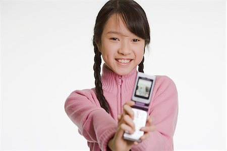 Happy girl using a mobile phone. Stock Photo - Premium Royalty-Free, Code: 6102-03905450