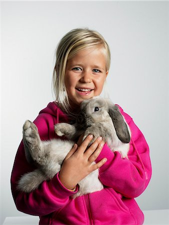 Portrait of a girl with a rabbit in her arms. Stock Photo - Premium Royalty-Free, Code: 6102-03905591