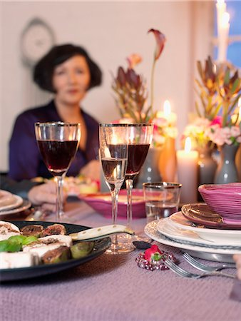 setting kitchen table - Woman seated at elegant dining table Stock Photo - Premium Royalty-Free, Code: 6102-03905883