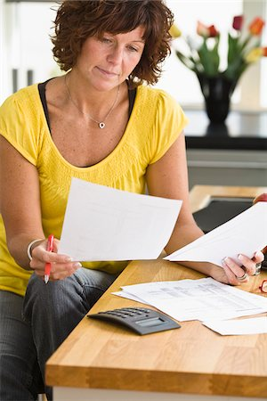 Woman sitting and looking through bills Stock Photo - Premium Royalty-Free, Code: 6102-04929441