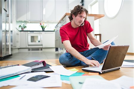 Mid- adult man struggling with domestic paperwork Stock Photo - Premium Royalty-Free, Code: 6102-04929523