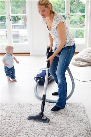 Mother vaccuming the livingroom Stock Photo - Premium Royalty-Free, Code: 6102-05655494