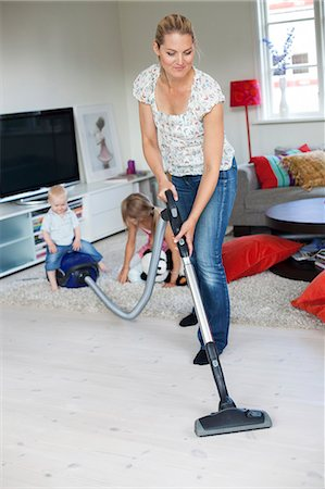 Mother vaccuming with her daughters playing in the background Stock Photo - Premium Royalty-Free, Code: 6102-05655495