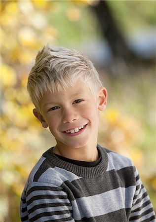 Portrait of blonde boy smiling outside Stock Photo - Premium Royalty-Free, Code: 6102-05802524
