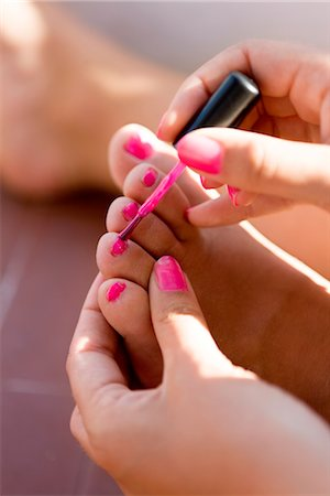 Close up of girls hand painting toenails with pink nail polish Stock Photo - Premium Royalty-Free, Code: 6102-05802609