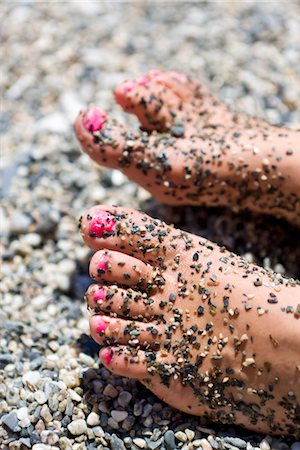 Close up of girls feet with pink nail polish covered with pebble stones Stock Photo - Premium Royalty-Free, Code: 6102-05802610