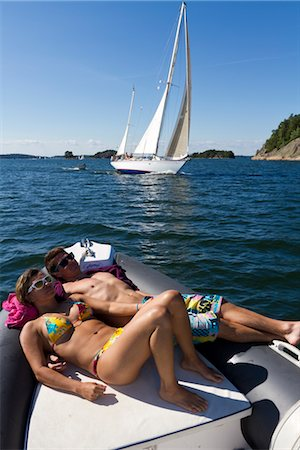 Young couple sunbathing on dinghy Stock Photo - Premium Royalty-Free, Code: 6102-05955870