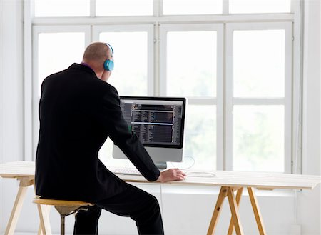 stockholm - Businessman listening to headphones, using computer in office Stock Photo - Premium Royalty-Free, Code: 6102-05955889