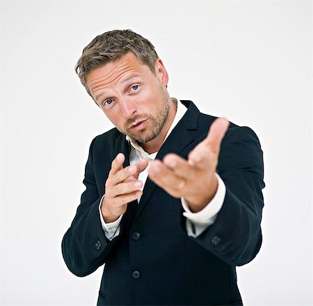 Studio portrait of businessman gesturing Stock Photo - Premium Royalty-Free, Code: 6102-06025852