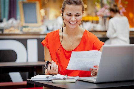 europe coffee shop - Young woman reading documents and talking on mobile phone using earbud Stock Photo - Premium Royalty-Free, Code: 6102-06025903