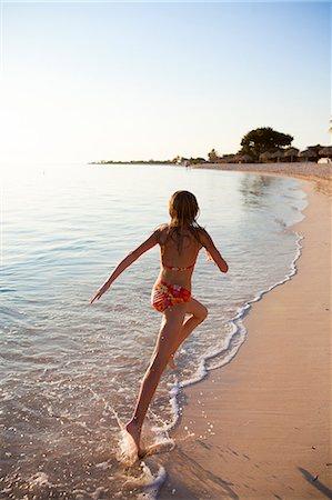 Girl running on beach Stock Photo - Premium Royalty-Free, Code: 6102-06374487