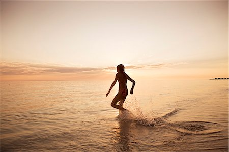 preteen girls bath - Silhouette of girl running into sea Stock Photo - Premium Royalty-Free, Code: 6102-06374490