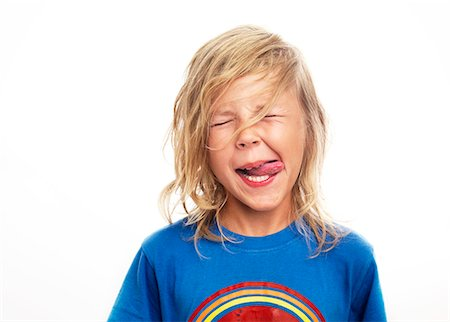 Portrait of boy sticking out tongue, studio shot Stock Photo - Premium Royalty-Free, Code: 6102-06336540