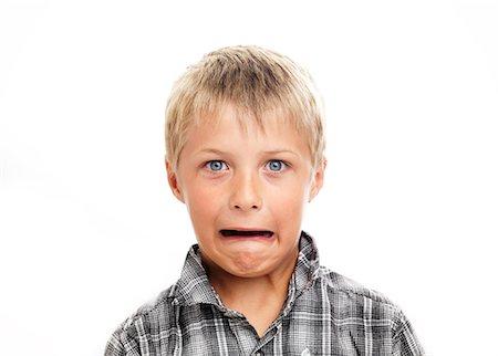 Portrait of boy making face, studio shot Stock Photo - Premium Royalty-Free, Code: 6102-06336547