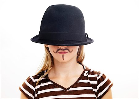 Portrait of girl wearing hat with fake moustache, studio shot Stock Photo - Premium Royalty-Free, Code: 6102-06336546