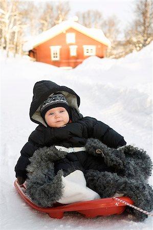 Baby girl sliding on toboggan in winter Stock Photo - Premium Royalty-Free, Code: 6102-06336587