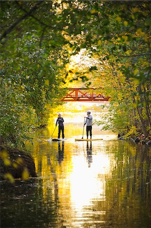 Two people rowing paddle boards in autumn trees Stock Photo - Premium Royalty-Free, Code: 6102-06336943