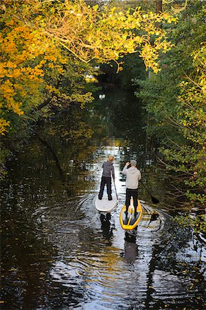 Two people rowing paddle boards in autumn trees, elevated view Stock Photo - Premium Royalty-Free, Code: 6102-06336940