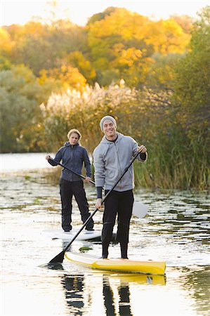 standing - Two people smiling on paddle boards on river Stock Photo - Premium Royalty-Free, Code: 6102-06336949