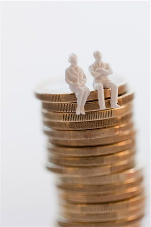 Stack of coins with figurines Stock Photo - Premium Royalty-Free, Code: 6102-06336984
