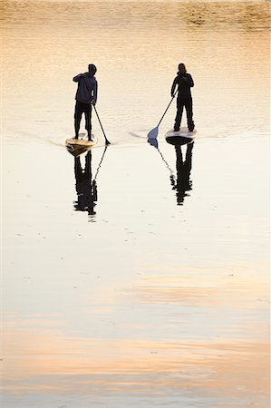 Two people rowing paddle boards in water at dusk, rear view Stock Photo - Premium Royalty-Free, Code: 6102-06336934