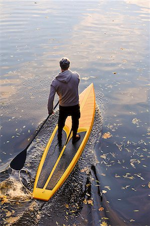 Man rowing paddle board in water, elevated view Stock Photo - Premium Royalty-Free, Code: 6102-06336936