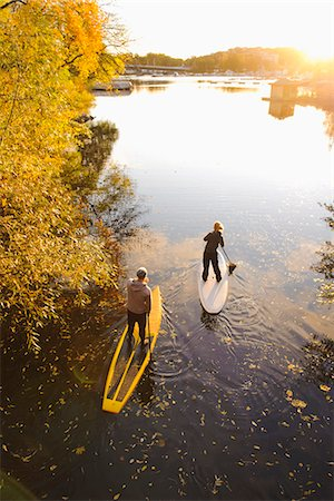 Two people rowing paddle boards in autumn trees, elevated view Stock Photo - Premium Royalty-Free, Code: 6102-06336938