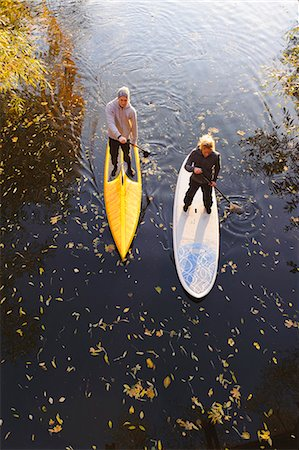 Two people rowing paddle boards in autumn trees, elevated view Stock Photo - Premium Royalty-Free, Code: 6102-06336939